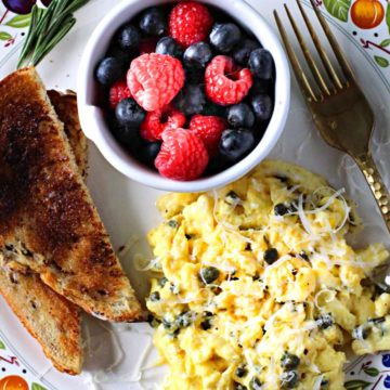 Scrambled eggs with capers served with toast and fresh berries