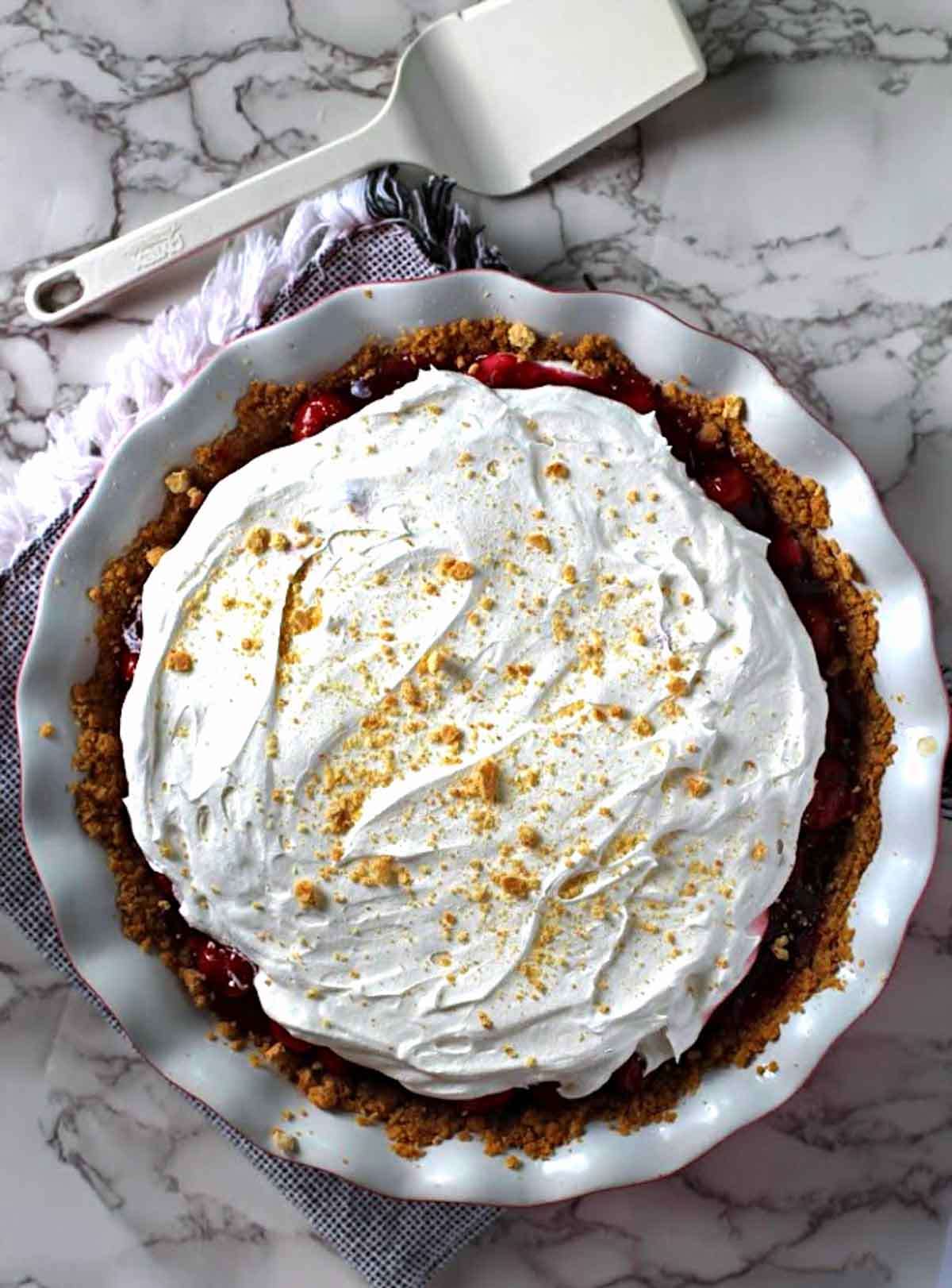 Cherry delight dessert in a pie pan topped with whipped cream