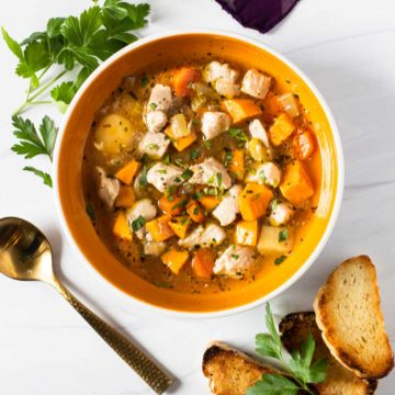 Chicken soup with sweet potatoes garnished with fresh parsley and toasted baguette