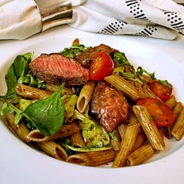 Steak salad recipe with sirloin beef, penne pasta, tomatoes, spinach in a white salad bowl.