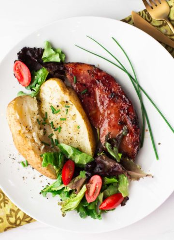 Glazed grilled ham steak with baked potato and lettuce salad garnished with chives