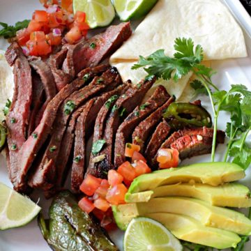 A platter of carne asada with avocado, lime, tomatoes and a flour tortilla