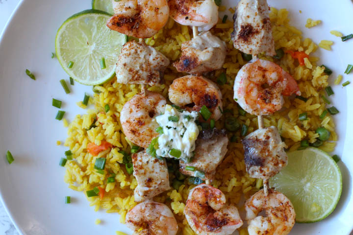Shrimp and Mahi Mahi on wooden skewers served on yellow Mexican rice, topped with a dollop of jalapeno butter and garnished with chives and lime slices