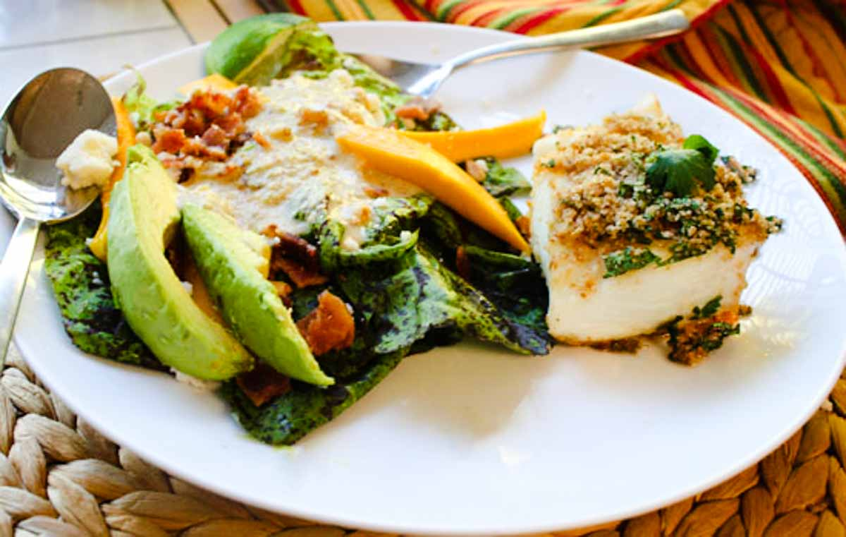 pan-seared halibut fillet topped with bread crumbs and cilantro served with a mango salad