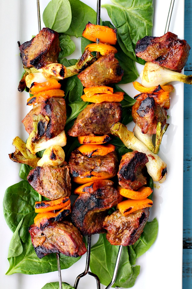 Sirloin steak beef kabobs with orange bell peppers, green onions on fresh spinach served on a white platter.