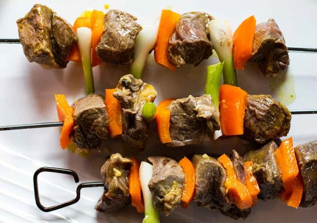 Metal skewers with sirloin steak chunks, orange bell pepper and green onion