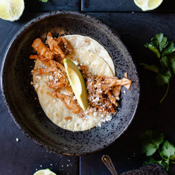 pork tacos on a soft corn tortilla topped with an avocado