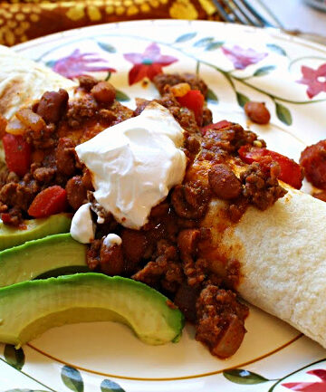 Chili burrito recipe, flour tortilla filled with smashed beans and cheese and topped with chili con carne. A dollop of sour cream and a side of sliced avocado.