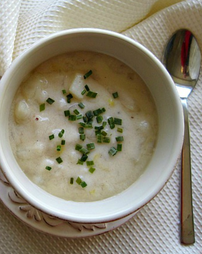 A white bowl filled with a cheesy potato soup recipe made with camembert cheese and cottage cheese