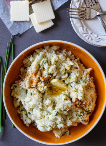 A bowl of mashed potatoes with poblanos and chives sprinkled with New Mexico Chile Powder
