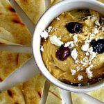 Yaya's hummus recipe topped with feta and olives served with slices of grilled pita