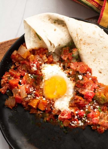 Easy huevos rancheros recipe with flour tortilla served with sauce