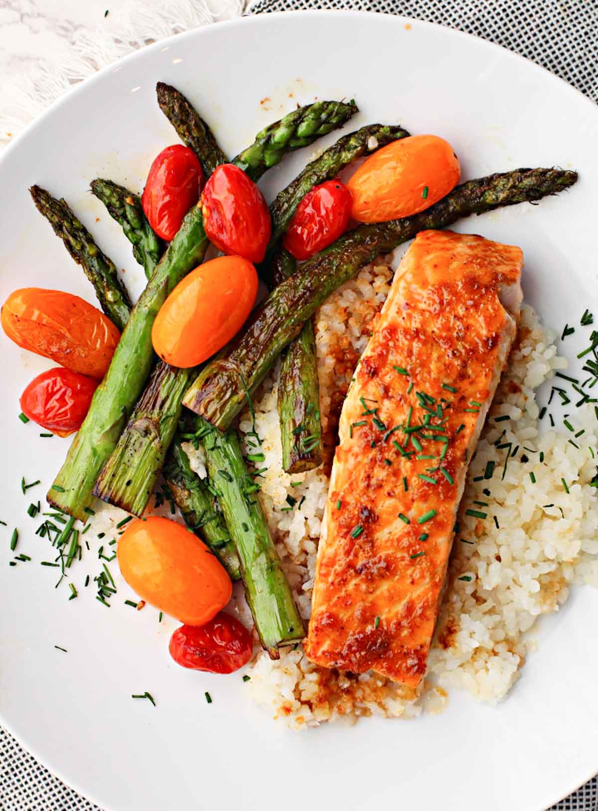 Salmon fillet glazed with mirin sweet cooking wine served over rice and sauteed asparagus and red and orange cherry tomatoes