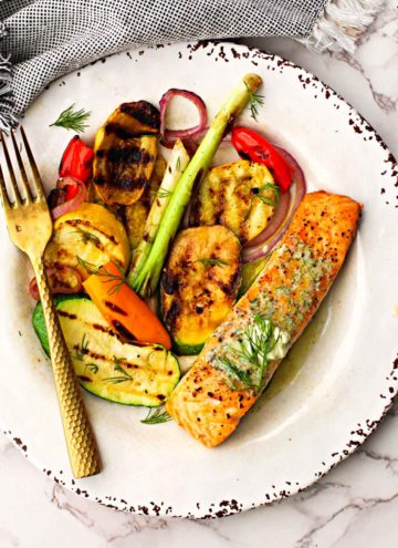 Grilled salmon fillet topped with dill butter served with grilled vegetables