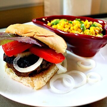 Hatch green chile burger on a plate with Mexican corn