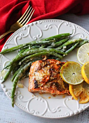 Lemon lime salmon topped with slices of lemon and limes and served with dijon cream green beans.