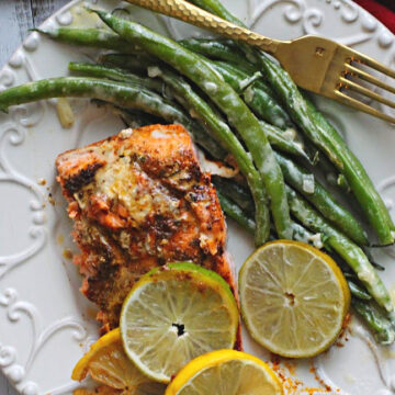 Lemon lime salmon with slices of lemons and limes served with french green beans.