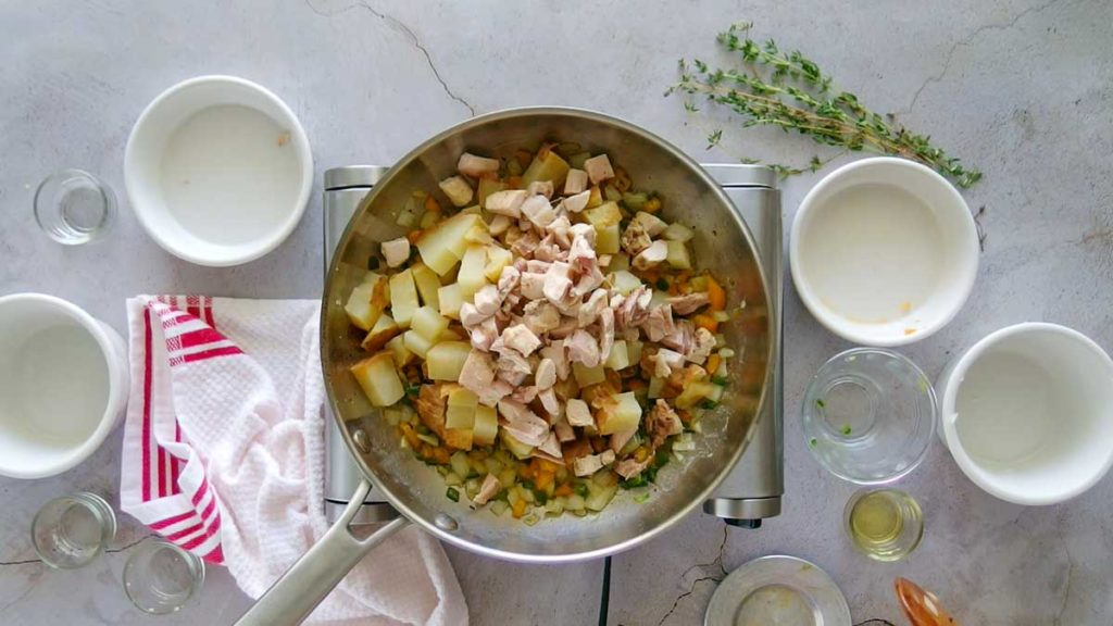 Adding chicken to vegetables and potatoes to make chicken hash