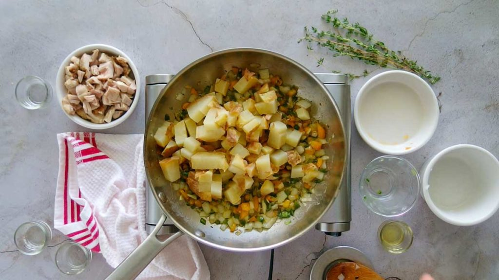 Adding potatoes to vegetables to make chicken hash