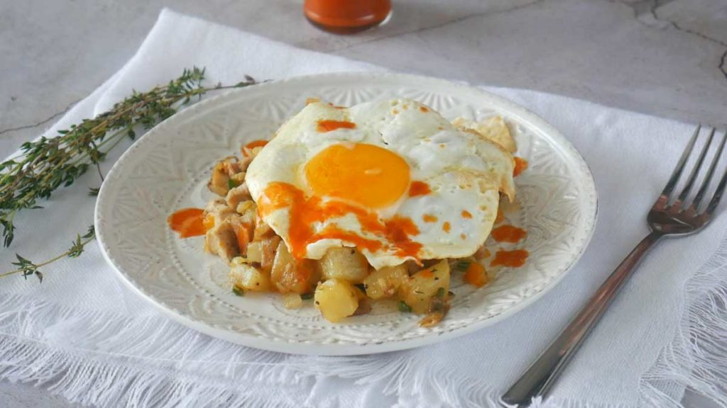 Chicken potato hash topped with a fried egg and drizzled with hot sauce.