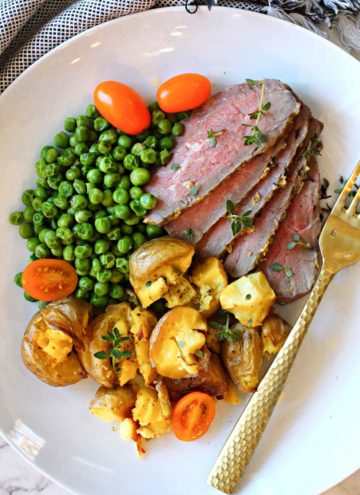 Baked tri-tip roast sliced and served with smashed potatoes and peas