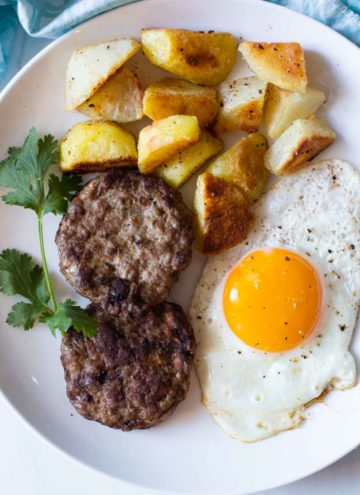 Homemade Turkey Sausage patties with a fried egg and fried potatoes