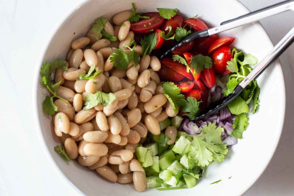 Mixing beans and chopped vegetables for shrimp and avocado salad