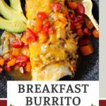 smothered breakfast burrito topped with cheese and diced tomatoes