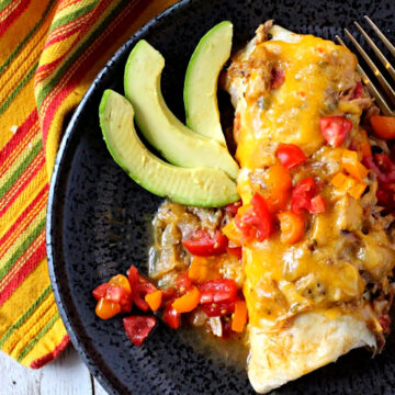 Green chile smothered brurrito topped with melted cheese and green chile and diced red and yellow tomatoes