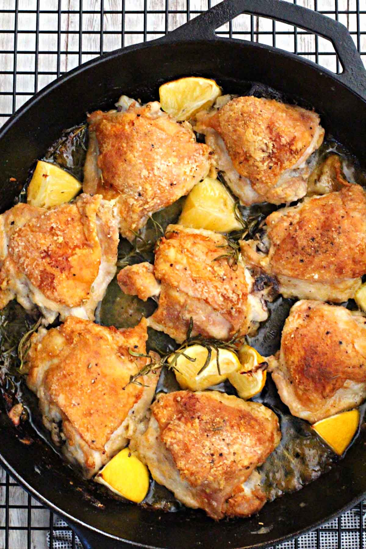 Cast Iron Skillet rosemary braised chicken thighs with lemon wedges cooking on a wire rack.