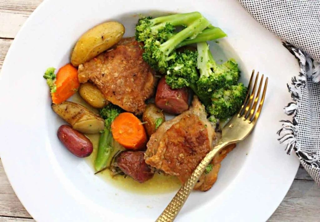Roasted chicken thighs with rosemary and served with broccoli, carrots and potatoes