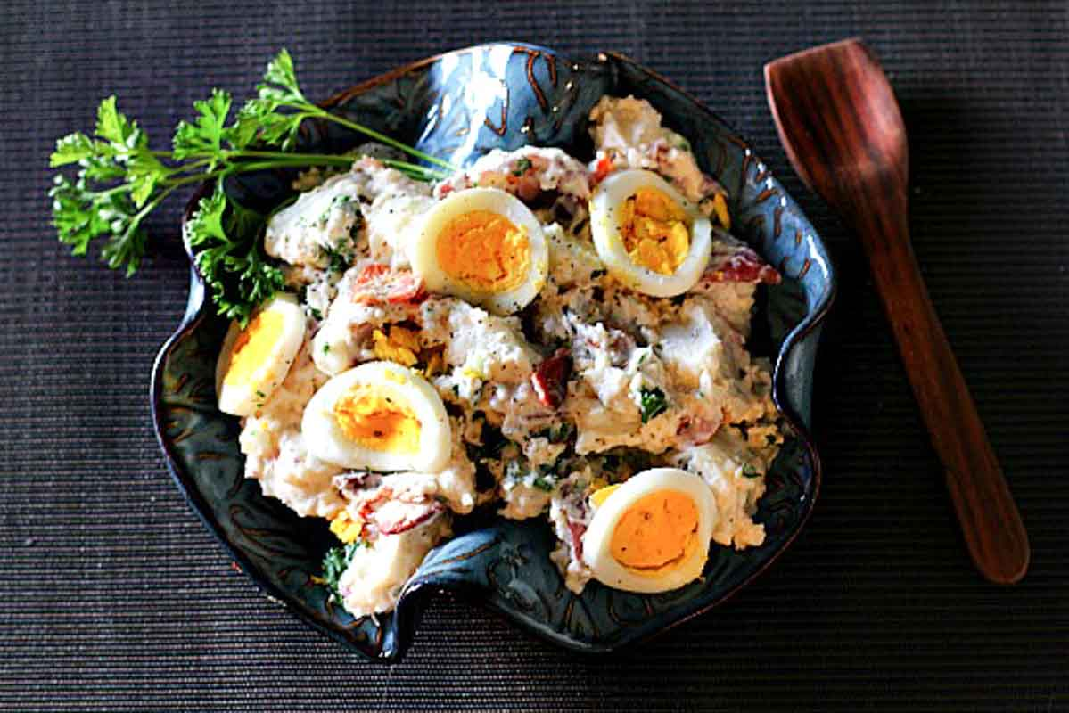 Bacon Blue Cheese Potato Salad in a blue ceramic bowl topped with sliced hard boiled eggs