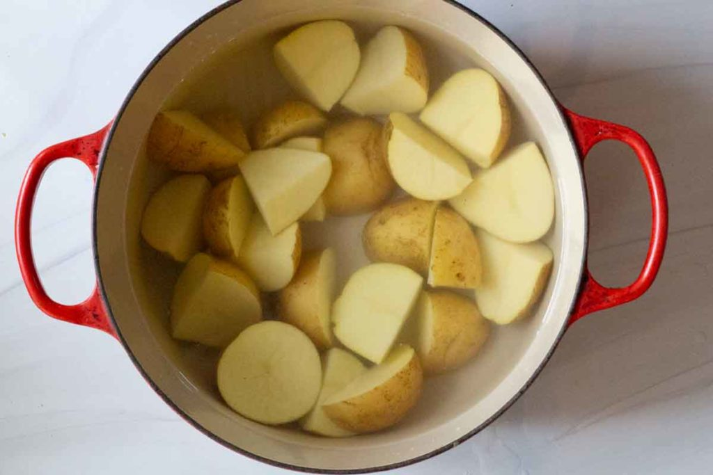 potatoes cut in cubes in a le creuset dutch oven covered with water