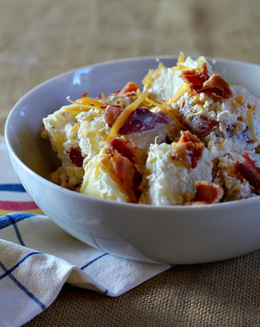 Potato salad with bacon and cheese in a white bowl.