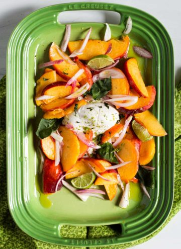 Salad with Peaches and Burrata on a green platter.