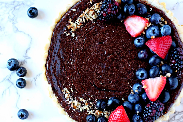 Creamy chocolate tart recipe topped with chopped nuts and barries