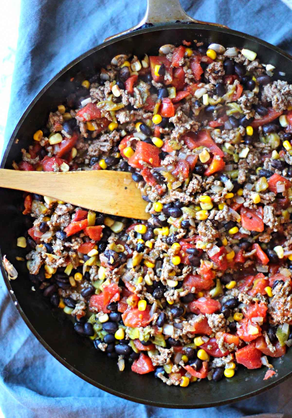 frying ground beef, tomatoes, beans and corn for a mexican casserole