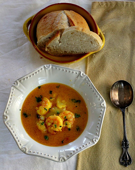 Bourride, French Cod and shrimpstew served in a white bowl with a side of French bread.