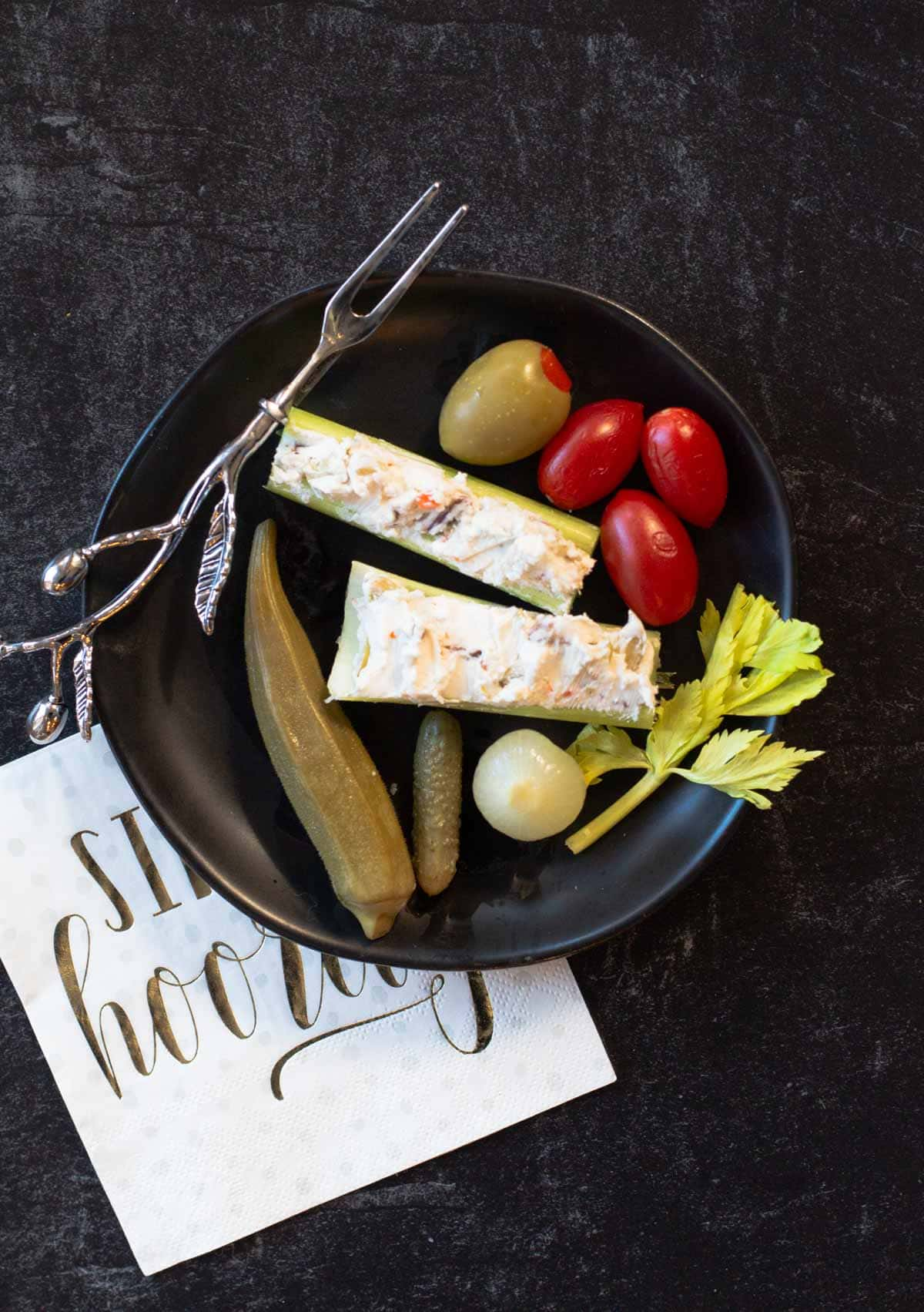 A black appetizer plate with cream cheese stuffed celery sticks, cherry tomatoes, and pickled okra