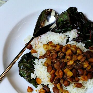 Chicos and beans, dried and smoked corn and pinto beans over rice and swiss chard
