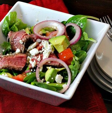 Steak salad with avocado and pickled onions.