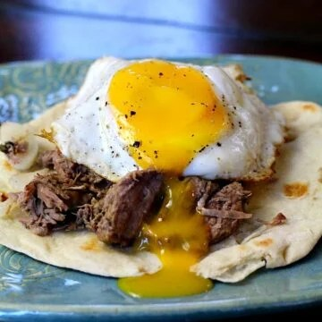 Beef Machaca Huevos. Mexican shredded beef is served on a flour tortilla and topped with an egg.