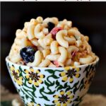 Pioneer Woman Macaroni Salad with black olives in a sunflower hand painted serving bowl.