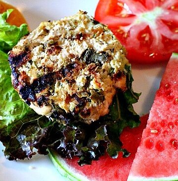 A chicken burger patty made with chopped hatch green chile on a bun with a slice of tomato and a slice of watermelon