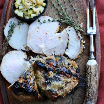 Pork loin roast on a cutting board with quick pickled cucumber relish