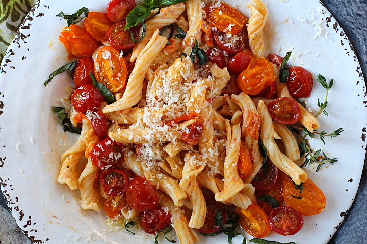 Pasta tossed with slow roasted cherry tomatoes topped with fresh basil and parmesan cheese