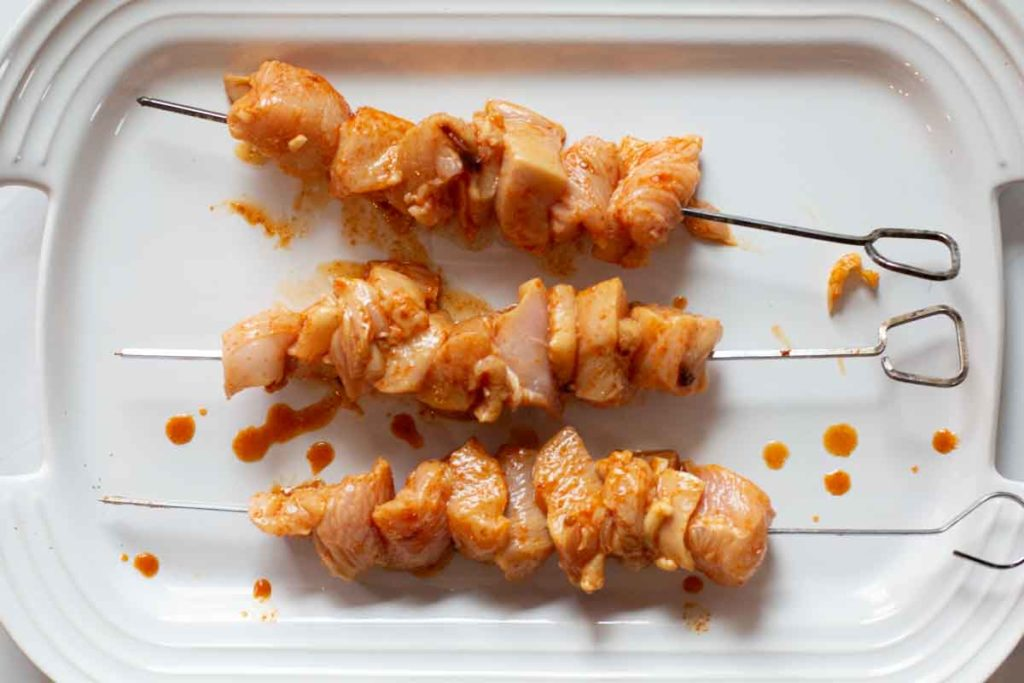ancho chile lime chicken kebabs on a white platter ready to grill