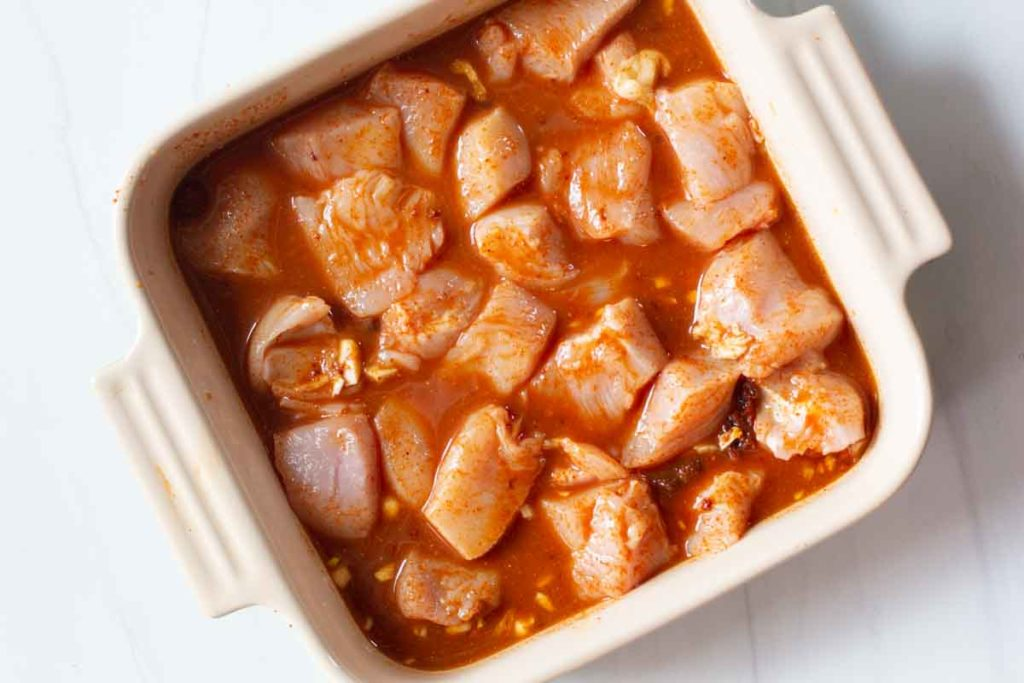 pieces of chicken breast marinating in chili lime sauce for chicken kebabs
