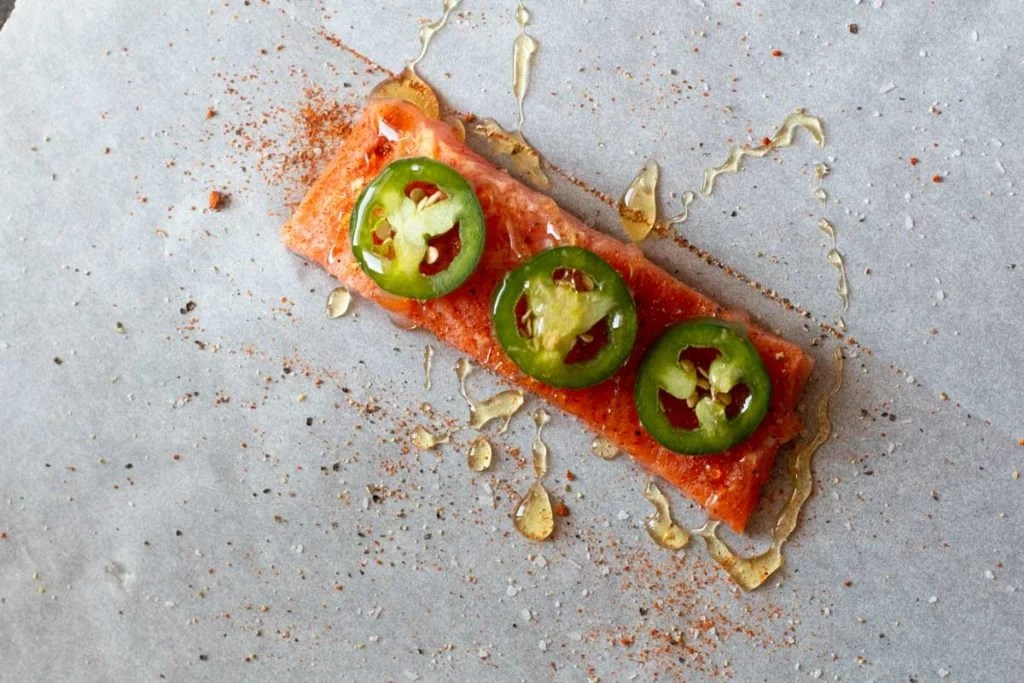 drizzling honey over a salmon fillet on parchment paper