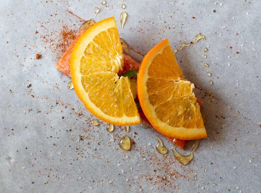 Sliced oranges on a salmon fillet on parchment paper